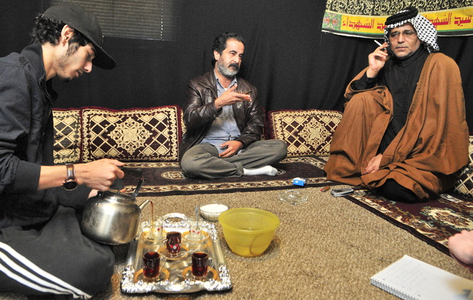 Coming to Augusta: Youssof Zamat, left, pours tea while Ghazi Yousif, center, answers questions during an interview last week at the apartment of Khalid Zamat, right, in Augusta.