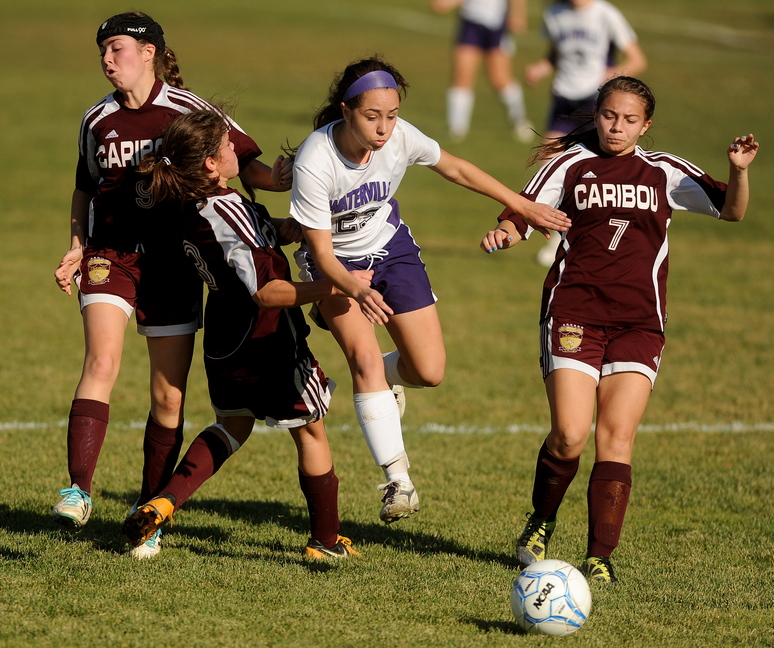 A BATTLE FOR THE BALL: Waterville Senior High School's Pilar Elias (23) battles through Caribou High School defenders, Erin Patton (9) far left, Eileen Patton, left center, and Emma Jandreau, right, in the first half in the Class B East semi-finals game in Waterville on Saturday. Waterville defeated Caribou 6-0.