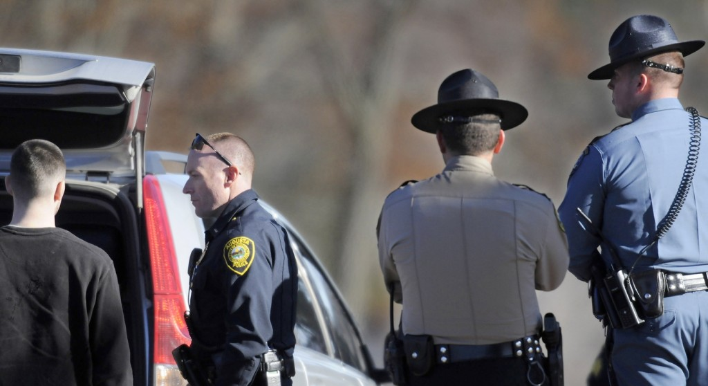SEARCH: Augusta police Lt. Kevin Lully, second from left, speaks with a man authorities stopped Wednesday afternoon while the man driving near Shaw's supermarket in Augusta a short time after the supermarket was robbed for the second time in two days. State, county and federal investigators assisted in the search for a suspect who ran away. The man being questioned was released after his vehicle was searched.