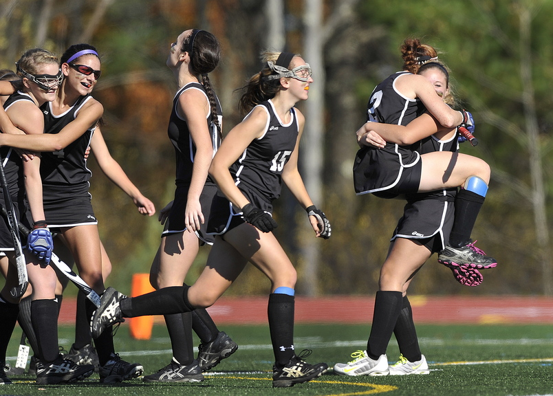 CELEBRATION TIME: Skowhegan's Renee Wright, (2) and Emily Trial, (23) embrace at far right as they celebrate their victory over Scarborough during the Class A field hockey state championship game at Yarmouth High School.