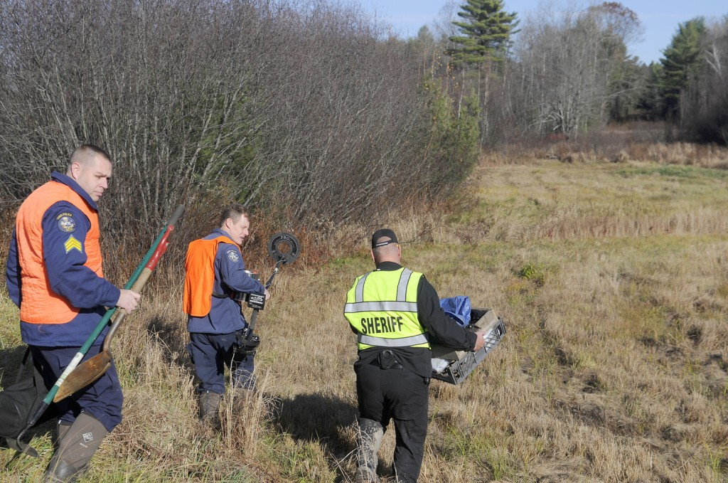 EXCAVATION: Maj. Ryan Reardon, right, of the Kennebec County Sheriff's Office, carries evidence collection tools; state police Detective Terry James, center, lugs a metal detector; and state police Detective Sgt. Jason Richards carries hand tools into the woods of Manchester on this afternoon to excavate skeletal remains discovered by hunters earlier in the day. The sheriff's department was called just after 8 a.m. when a deer hunter encountered the bones about a half-mile up a dirt logging road from Puddledock Road, according to Reardon. The remains, believed to be of an adult, will be examined as they are recovered to determine an identity and a cause of death, Reardon said.