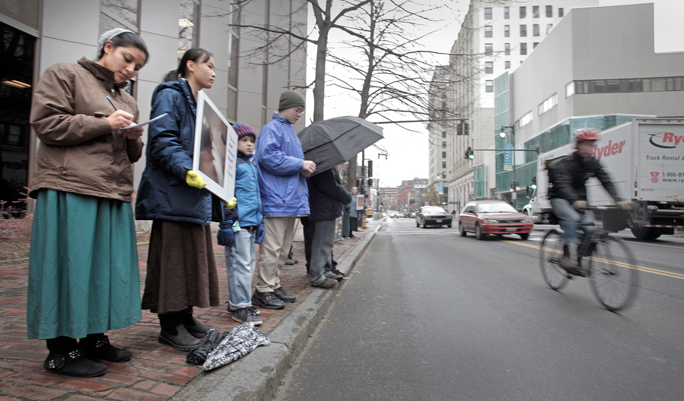 Anti-abortion protesters stand across the street from the Planned Parenthood clinic in Portland on Friday, the first day that protesters have picketed the Congress Street clinic since a 39-foot buffer zone around Planned Parenthood took effect.