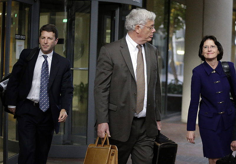 Harold McIlhenny, center, an attorney representing Apple Computer in the Apple Samsung trial, exits a federal courthouse Wednesday, Nov. 13, 2013, in San Jose, Calif. How much does Samsung Electronics owe Apple for copying vital features of the iPhone and iPad, such as scrolling and the