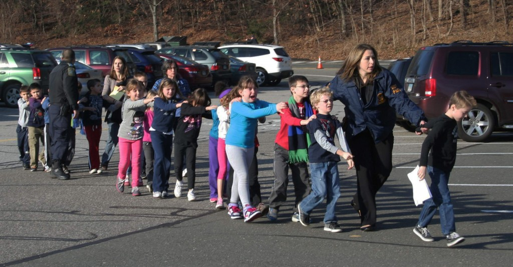 In this photo provided by the Newtown Bee, Connecticut State Police lead a line of children from the Sandy Hook Elementary School in Newtown, Conn. on Friday, Dec. 14, 2012 after a shooting at the school. Recordings of 911 calls from the Newtown school shooting are being released Wednesday Dec. 4, 2013, days after a state prosecutor dropped his fight to continue withholding them despite an order to provide them to The Associated Press.