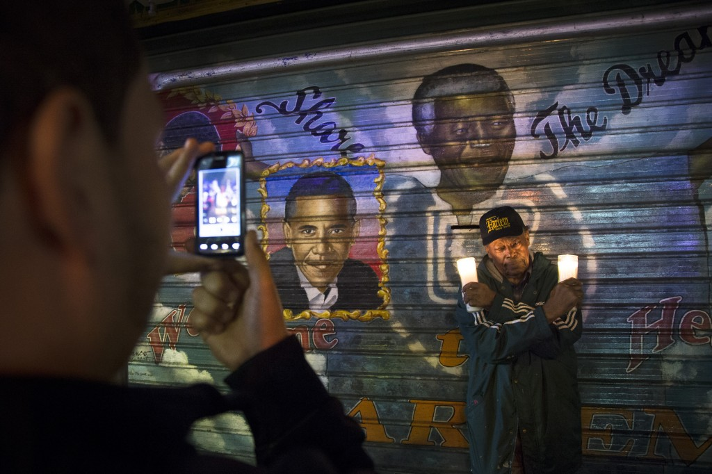"""A man takes a picture of an artist who goes by the name """"Franco the Great"""" in front of a mural of South African leader Nelson Mandela that the artist painted in 1995, and later added U.S. President Barack Obama, on 125th Street in the Harlem neighborhood of New York, Thursday, Dec. 5, 2013. Mandela, South Africa's first black president, died Thursday after a long illness. He was 95."""