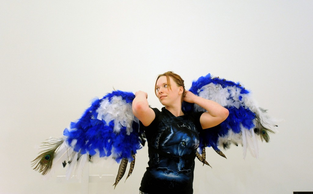 """Wings: Maeve-Wolf O'Reiley, 21, a sculpture student at the University of Maine at Farmington, tries on her prosthetic creation titled """"Flights of Fantasy"""" during a set-up Wednesday for the campus exhibition. O'Reiley used more than 700 feathers and spent more than two weeks creating the winged prosthesis."""