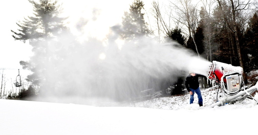 MAKING SNOW: Dave Beers, owner of Eaton Mountain in Skowhegan, adjusts one of the new snow guns that was making snow on the snow tubing hill on Wednesday. Beers said the facility will open this Saturday.