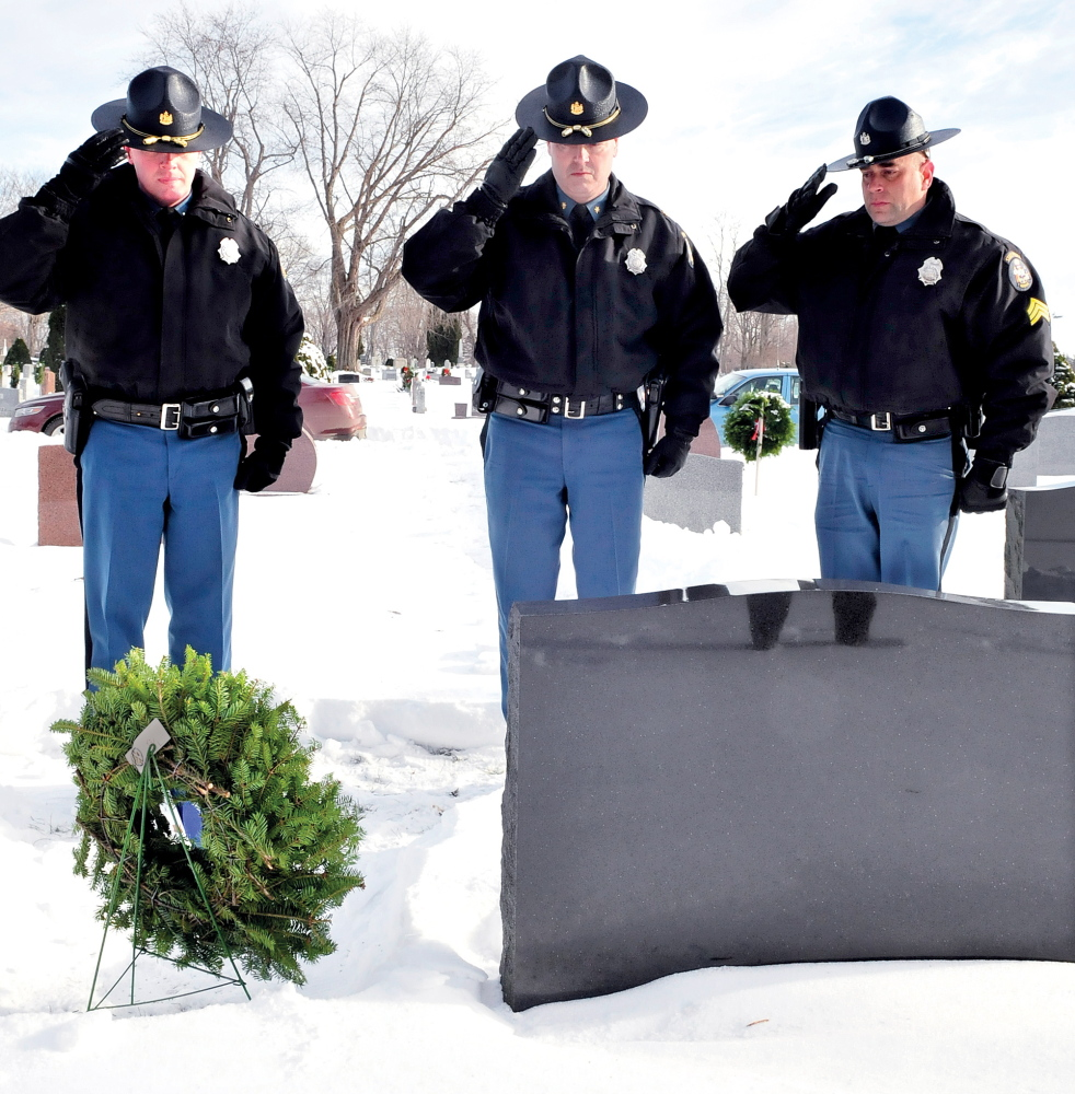 PAYING RESPECT: Maine State Police troopers salute at the gravesite of Trooper Jeffrey Parola at St. Francis Cemetery in Waterville after placing a wreath on it Tuesday. Troopers who have died in the line of duty were recognized at other cemeteries as well. From left are Lt. Scott Ireland, Maj. Gary Wright and Sgt. Mike Zabarsky.