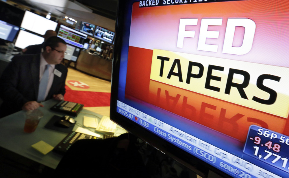 A television screen at a trading post on the floor of the New York Stock Exchange shows the decision of the Federal Reserve, Wednesday, Dec. 18, 2013. The Federal Reserve has decided to reduce its stimulus for the U.S. economy because the job market has shown steady improvement. The Fed will trim its $85 billion a month in bond purchases by $10 billion starting in January.