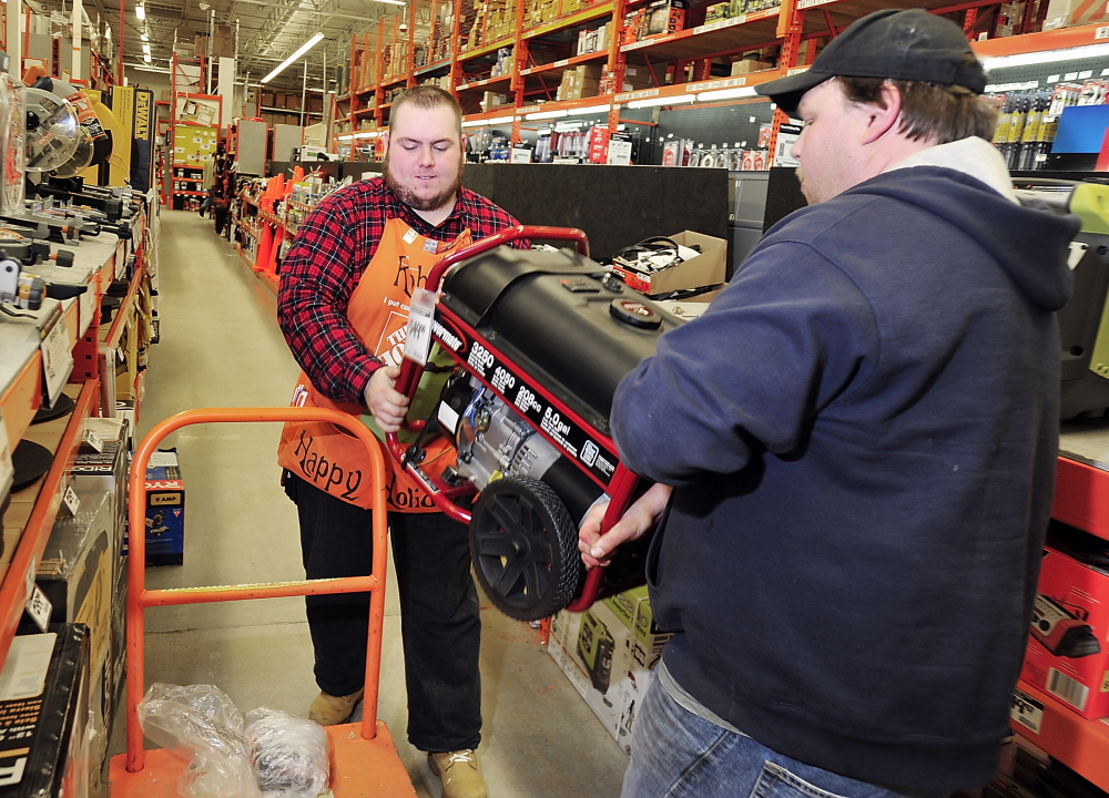 Josh Newell of Standish, right, helps Robert Muldowney, a hardware sales associate at the Home Depot in Portland, load a generator onto a cart for his mother in anticipation of possible electrical outages this weekend.