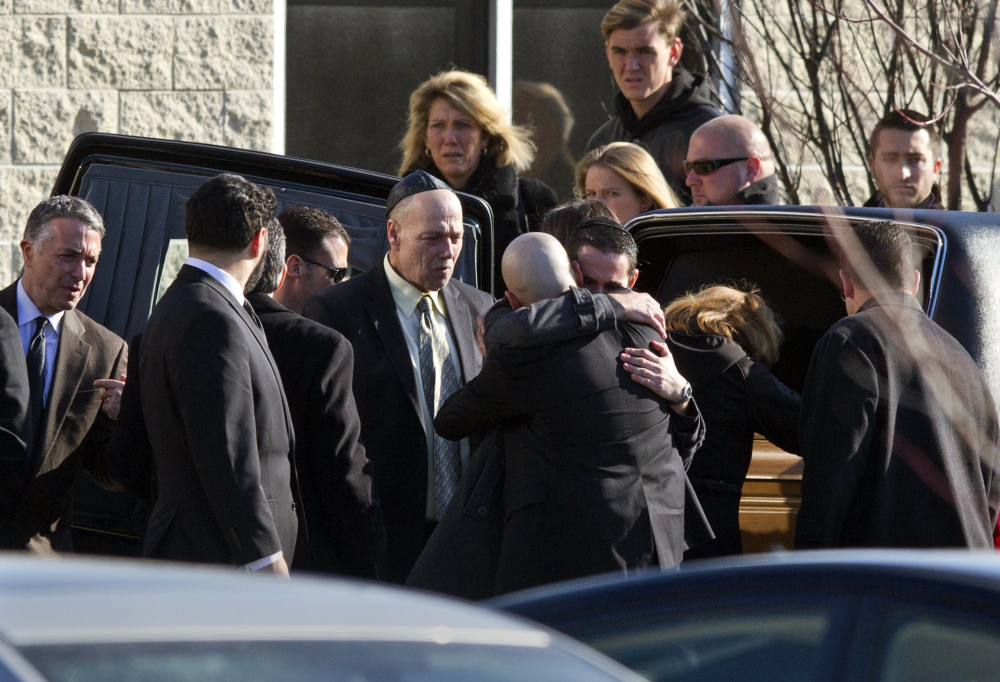 Mourners grieve outside the temple after the funeral service for Daniel Friedland Wednesday in Lakewood, N.J. Friends and relatives gathered to mourn the 30-year-old lawyer who was shot to death by a carjackers outside a northern New Jersey mall last weekend.