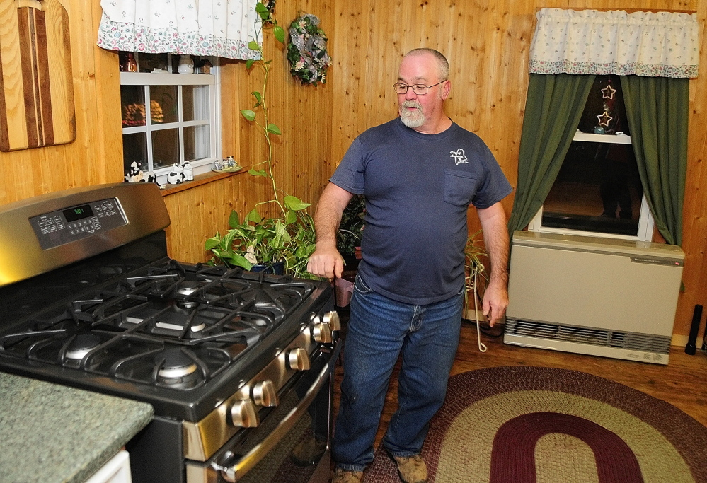 Switched: Dick Gagnon talks about the five burner kitchen stove, left, and direct vent heater, bottom right, that now run on natural gas in his Augusta home. Gagnon recently switched from propane to natural gas.