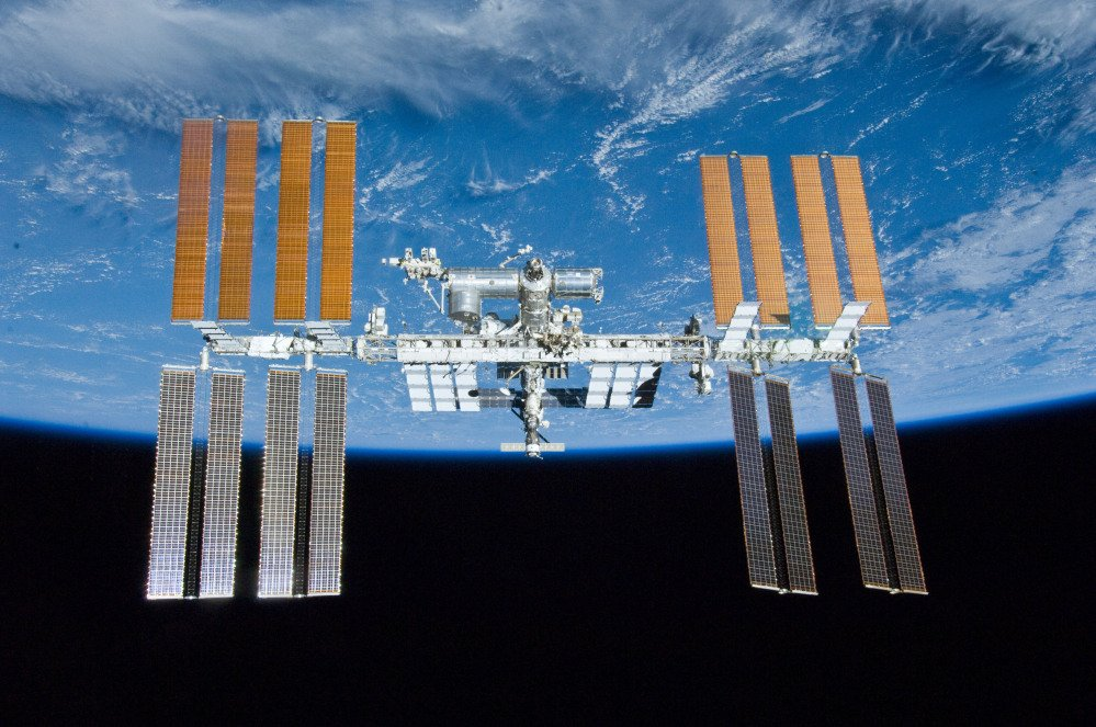 The International Space Station with the Earth in the background. NASA decided to schedule a series of urgent spacewalks to fix a broken cooling line at the International Space Station.