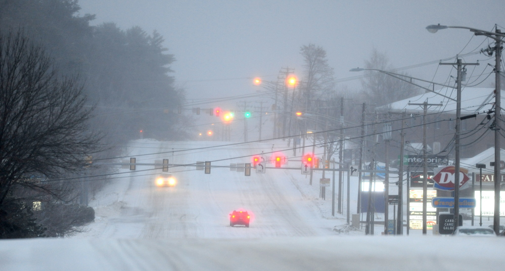 ICEY DICEY: Traffic moves slowly on Kennedy Memorial Drive in Waterville early Sunday morning as a major ice storm grips the area.