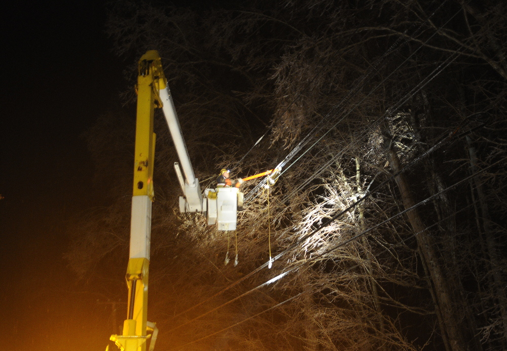 POWER UP: An employee of electrical contractor Coutts Brothers hangs a power line Monday night in Hallowell. Thousands across Maine remain without power because of an ice storm that coated lines and limbs.