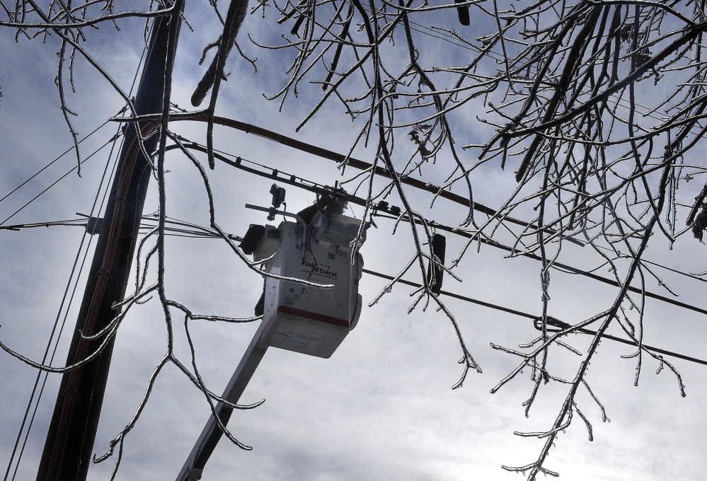 Staff photo by Andy Molloy CONNECTIONS: FairPoint Communications splicer Jason Fredette hooks up a line on a pole in Richmond on Tuesday. Utility crews from across New England descended upon Kennebec County to repair utility lines snapped by frozen limbs.