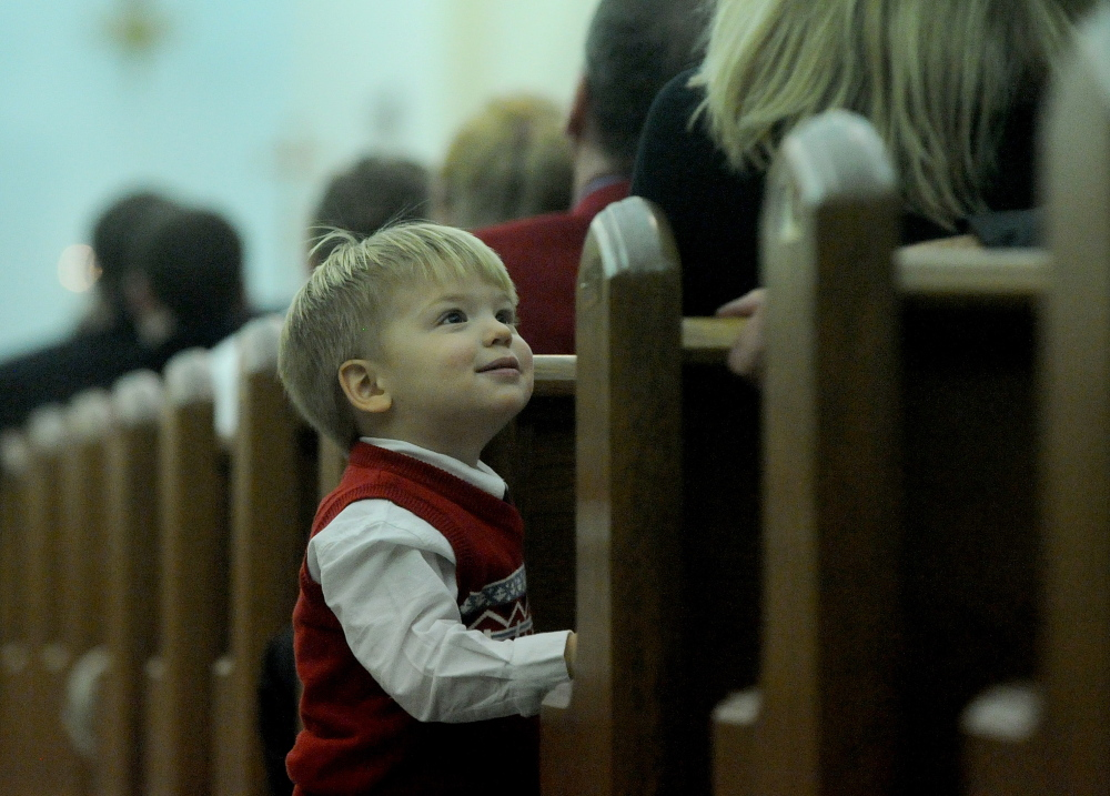 Staff photo by Michael G. Seamans CHRISTMAS IN WATERVILLE: Brody Jabar, 1, looks to his mother for some entertainment Heather during the Christmas Eve Liturgy at St. Joesph's Maronite church in Waterville on Tuesday, Dec. 24, 2013.