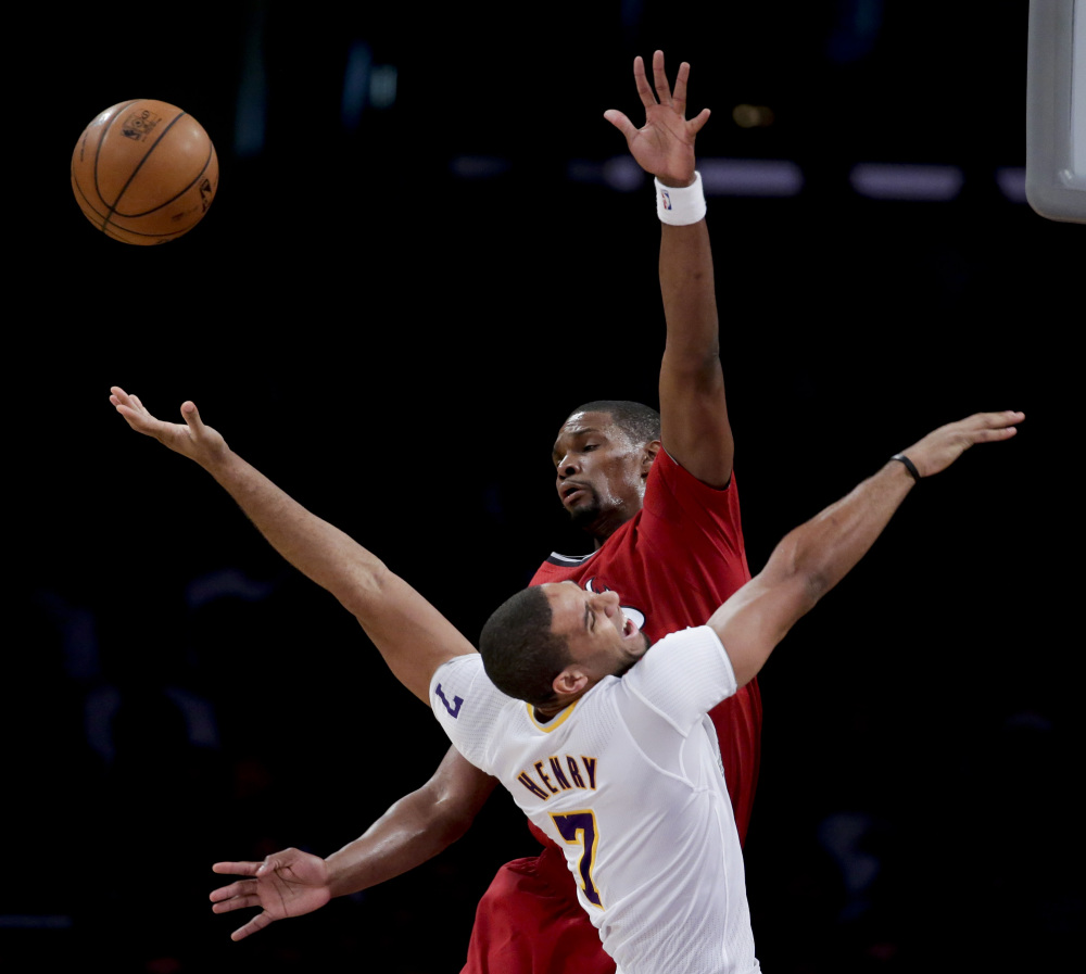 BIG NIGHT: Miami Heat center Chris Bosh, top, blocks a shot by Los Angeles Lakers forward Xavier Henry during the second half of their game Wednesday in Los Angeles. The Heat won 101-95.