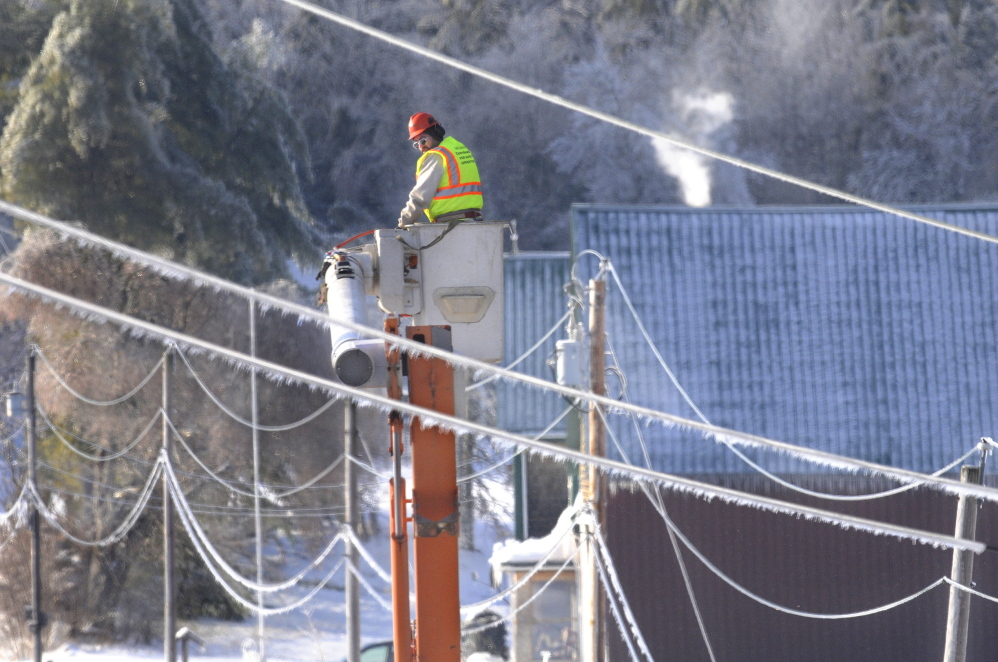 Staff photo by Andy Molloy ICE OUT: Asplundh Tree Expert Co arborist Randy Patten descends between frozen power lines Wednesday in Farmingdale after clearing limbs away from utility poles. Several hundred out of state utility and tree workers arrived in Kennebec County on Christmas to restore power. Patten travelled from Vermont with fellow arborist Ray Coutu to remove fallen branches overhanging hazardous power lines.