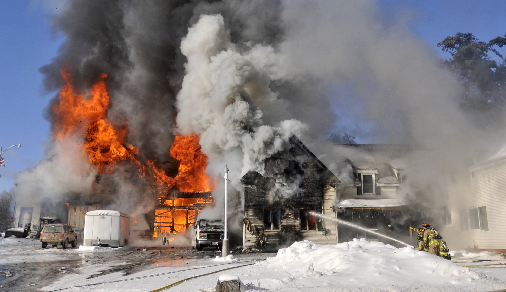 Staff photo by Michael G. Seamans CHRISTMAS FIRE: Firefighters from Waterville battle a blaze at 160 Drummond Ave. in Waterville on Wednesday.