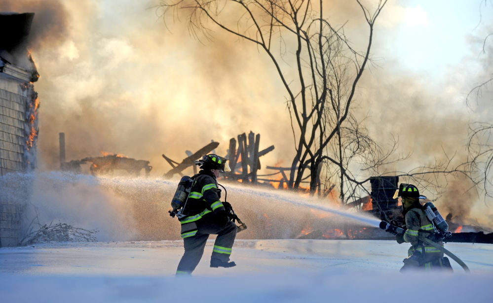 Staff photo by Michael G. Seamans CHRISTMAS FIRE: Fairfield firefighters battle a fire at 160 Drummond Ave. in Waterville on Wednesday.