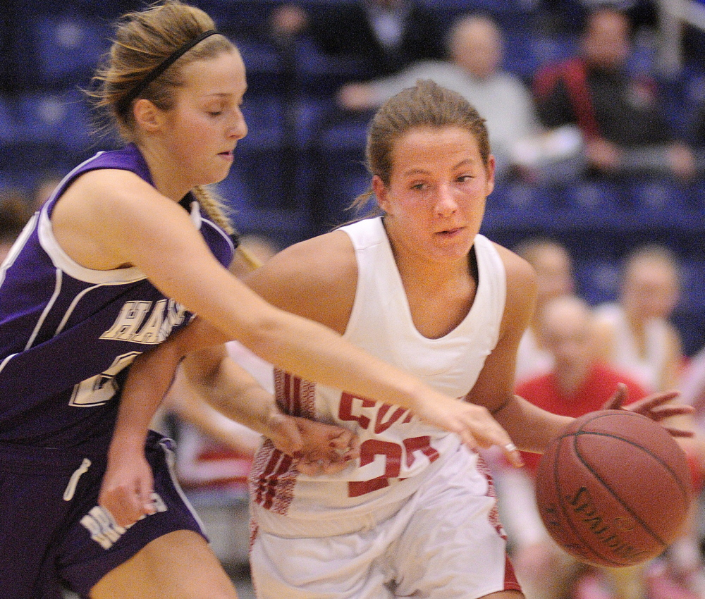 Staff photo by Andy Molloy MOVE OVER: Cony High School's Hayley Quirion, right, dribbles past Hampden Academy's Elise Arsenault Friday during a basketball match up in Augusta during the Capital City Hoop Classic.