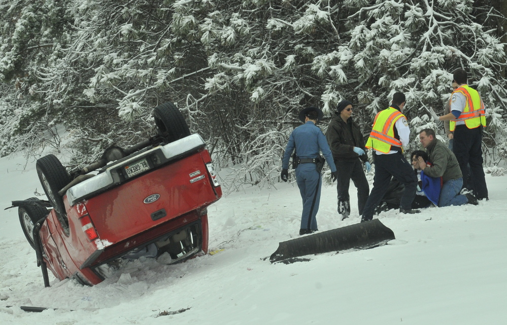 interstate crash: Emergency responders and others aid a person at a one-truck accident Saturday afternoon on Interstate 95 in Sidney. The pickup truck crashed a short distance beyond where the Town Farm Road passes over the interstate.