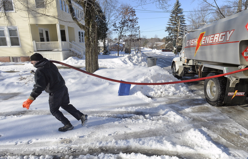 Tim Darnell of Cash Energy heads up a snowy, icy driveway Monday while delivering oil in Portland. Steep and slick driveways and snow-clogged back roads are making deliveries difficult in some areas.