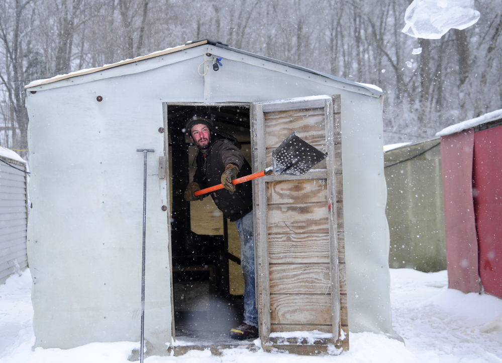 CLEANING OUT: Mike Abbott tosses ice out of a smelt shack Thursday at Baker's Smelt Camps in Pittston. Abbott cleaned the ice out of race holes at the camps on the Kennebec River before anglers arrived to fish an afternoon tide.