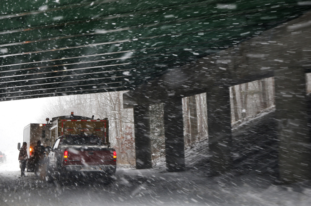 A salt and sand road crew regroups under a bridge as snow falls in Andover, Mass., on Thursday. Up to 14 inches of snow is forecast for the Boston area.