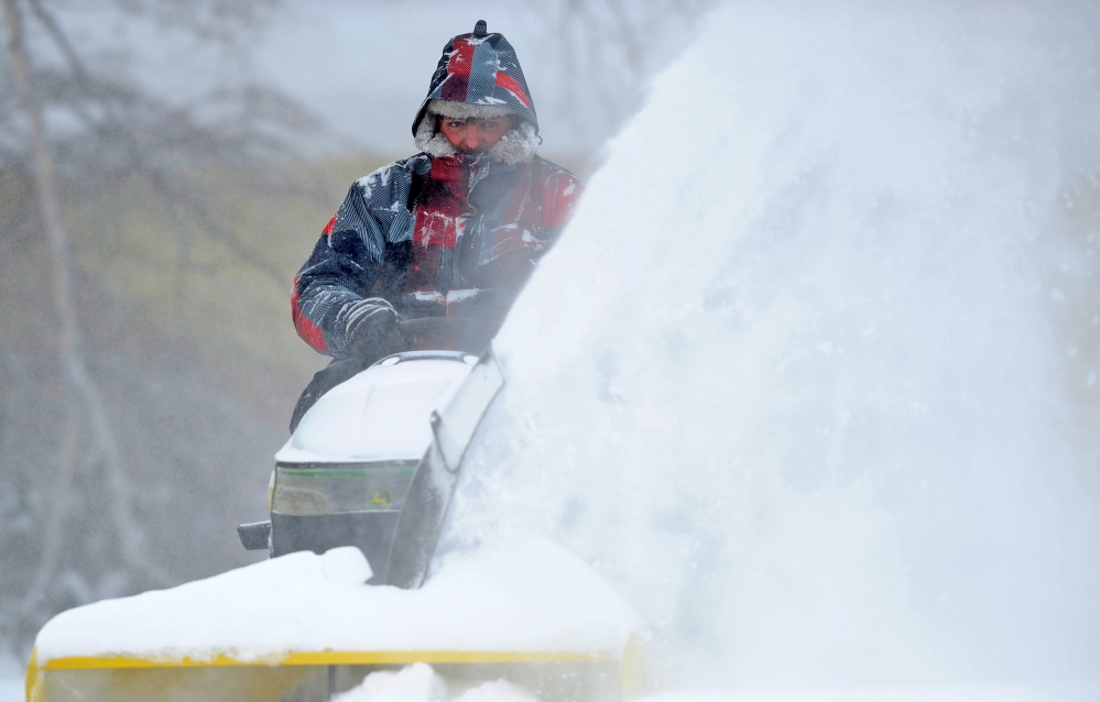 DEEP FREEZE: Mark Douglas clears his Mayflower Hill Road neighbor's driveway after more snow blankets Waterville on Friday.