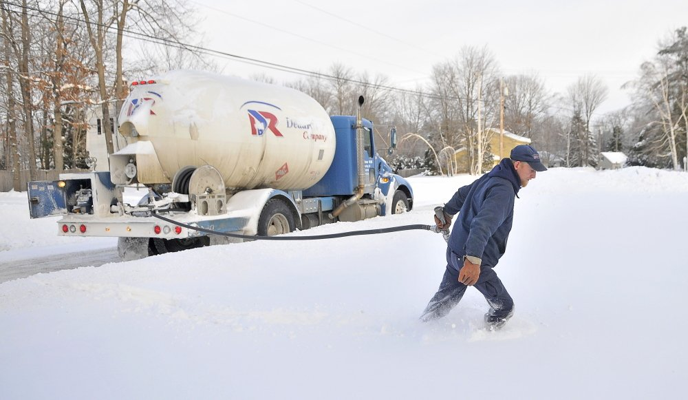 """Staff photo by Michael G. Seamans WINTER HEAT: Greg French, a 15-year veteran delivery man for Dead River Oil, trudges through deep snow to make a delivery on Primrose Street in Winslow on Friday. French said it has been busier than usual compared to previous years. """"We haven't seen cold like this in a long time. Usually there is a bit of relief with a thaw. Not this year,"""" French said."""