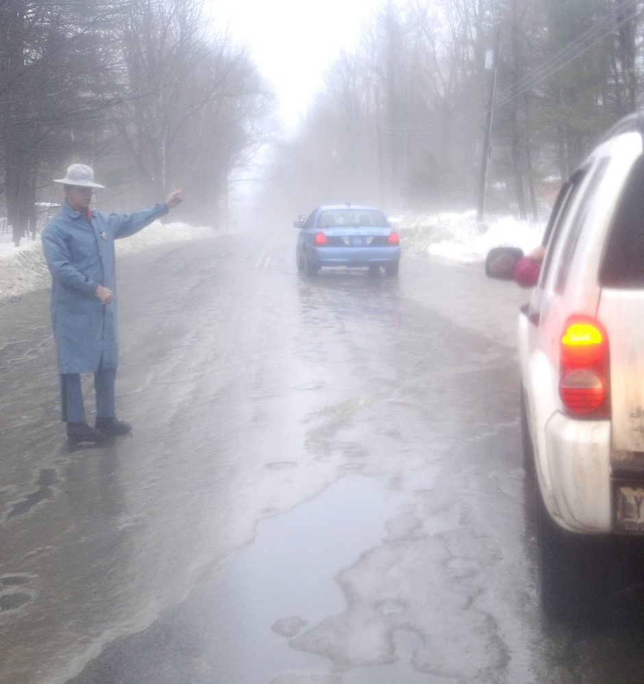 ELEMENTS: State Trooper Sam Tlumac directs traffic away from icy roads Monday morning on Northern Avenue in Farmingdale. Drivers encountered icy roads slickened by rain compelling authorities to close several roads across the state.