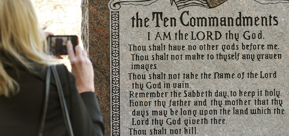A woman takes a picture of a granite monument engraved with the Ten Commandments after it was erected on the north side of the state Capitol grounds in Oklahoma City in 2012. A group of New York-based Satanists now want to erect their own monument depicting a goat-headed deity.