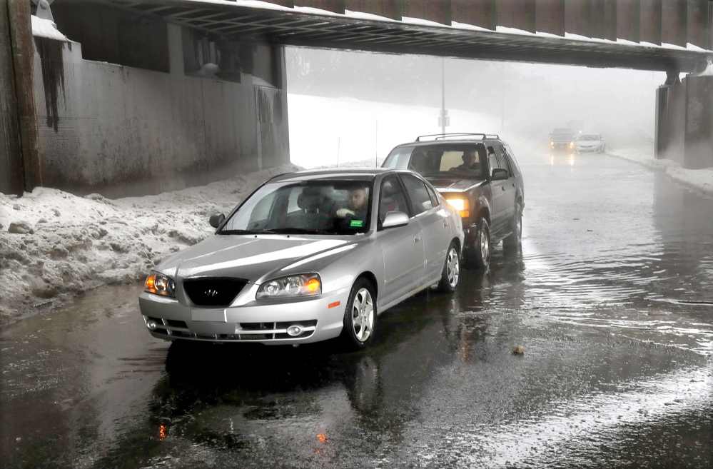 PUSHED OUT: Motorist Derek Archer, in the front car, is pushed out of a foot of water on College Avenue in Waterville during steady rain on Monday. Mark Farino came along and slowly pushed Archer's vehicle out. Area streets and roads were flooded as drains were plugged and could not handle the volume of water.