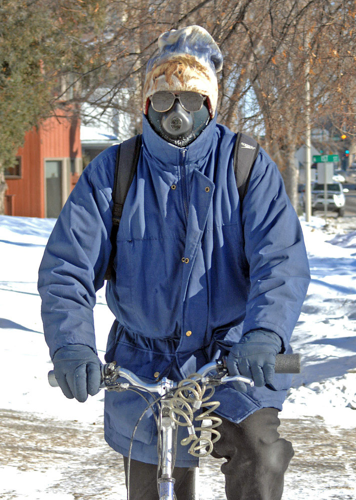 Jon Kramer, of Bismarck, N.D., said a good way to beat the cold conditions is with a face mask called the cold avenger. Kramer uses the unusual looking face mask to break the wind as he rides his bicycle on Monday.