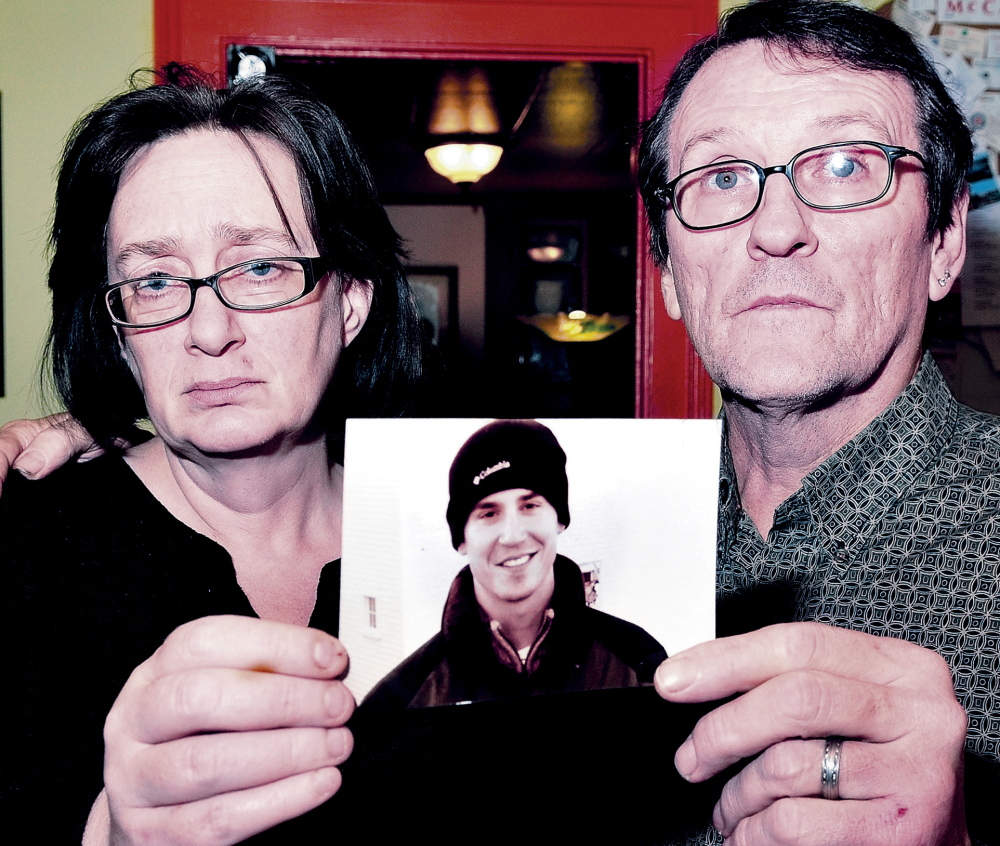 TRAGIC END: Lorna and Michael Smilek hold a 2006 photograph of Michael's son, Justin Crowley-Smilek, who was shot and killed after he confronted Farmington police in 2011.