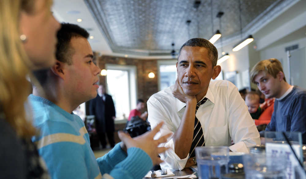 President Barack Obama listens to Andres Cruz, second from left, as he has lunch with five young people at The Coupe restaurant in the Columbia Heights section of Washington on Friday. The five are spearheading creative outreach efforts to connect with and help enroll young consumers in the new health care marketplaces. Seated at the table with Obama at left is Anne Johnson.