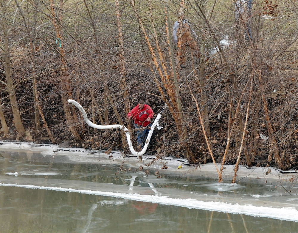 A Freedom Industries worker places a boom in the Elk River on Thursday at the site of a chemical leak in Charleston that has fouled the drinking water in five West Virginia counties.