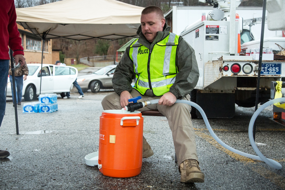 Police Chief Brian Oxley helps distribute water Saturday in Nitro, W.Va., after a chemical spill Thursday in Charleston.