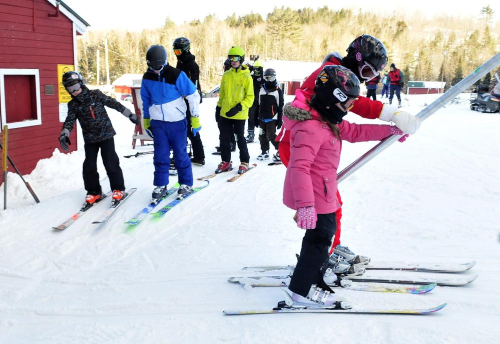 UPWARD: Skiers and snowboarders ride a T-bar lift at Titicomb Mountain Ski Area in Farmington.