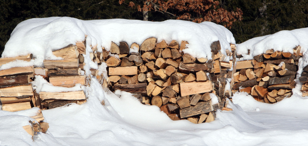 Stacks of wood are seen at the town transfer station in Hopkinton, N.H. Like a food bank, several communities in northern New England run by church groups, social services agencies and towns, have set up wood piles for needy residents to get wood through the cold winters. (AP Photo/Jim Cole)