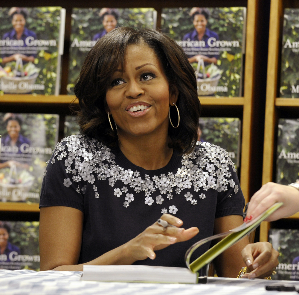"""Michelle Obama signs copies of her book, """"American Grown: The Story of the White House Kitchen Garden and Gardens Across America,"""" at a bookstore in Washington in May. The nation's first lady turns 50 on Friday and, by her own account, feels more relaxed now that President Barack Obama's days as a candidate for elected office are over."""