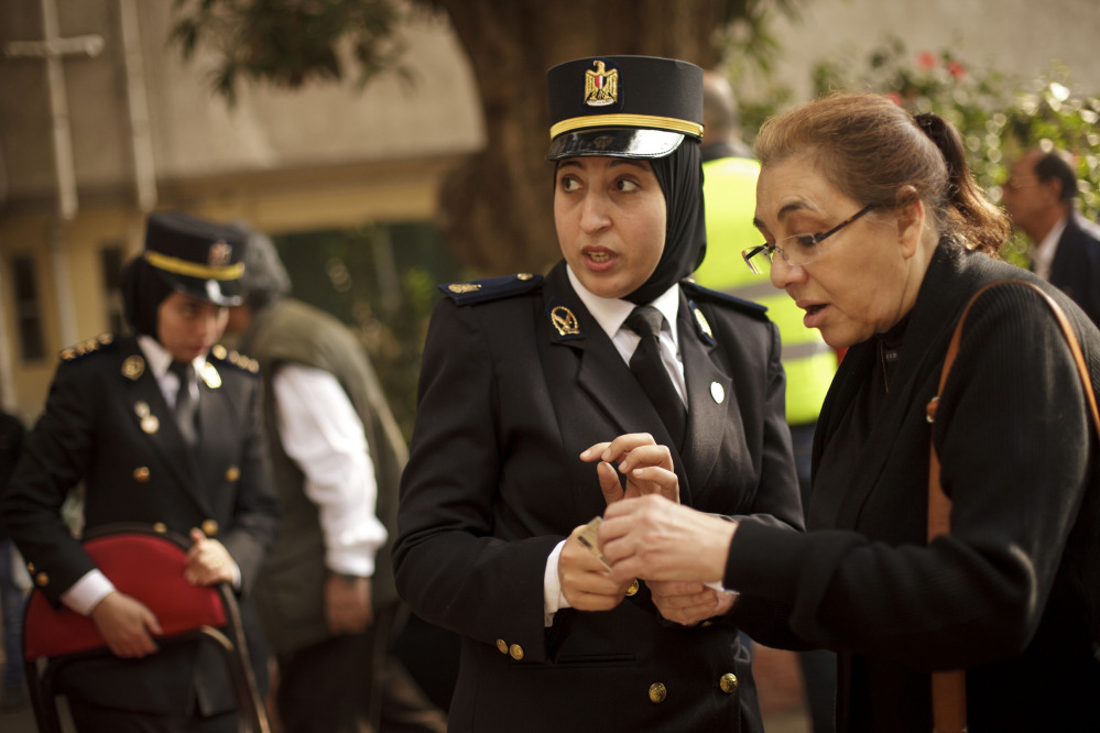 An Egyptian policewoman directs a woman at a polling site on the first day of voting in the country's constitutional referendum in the upscale Zamalek neighborhood of Cairo, Egypt, on Tuesday.