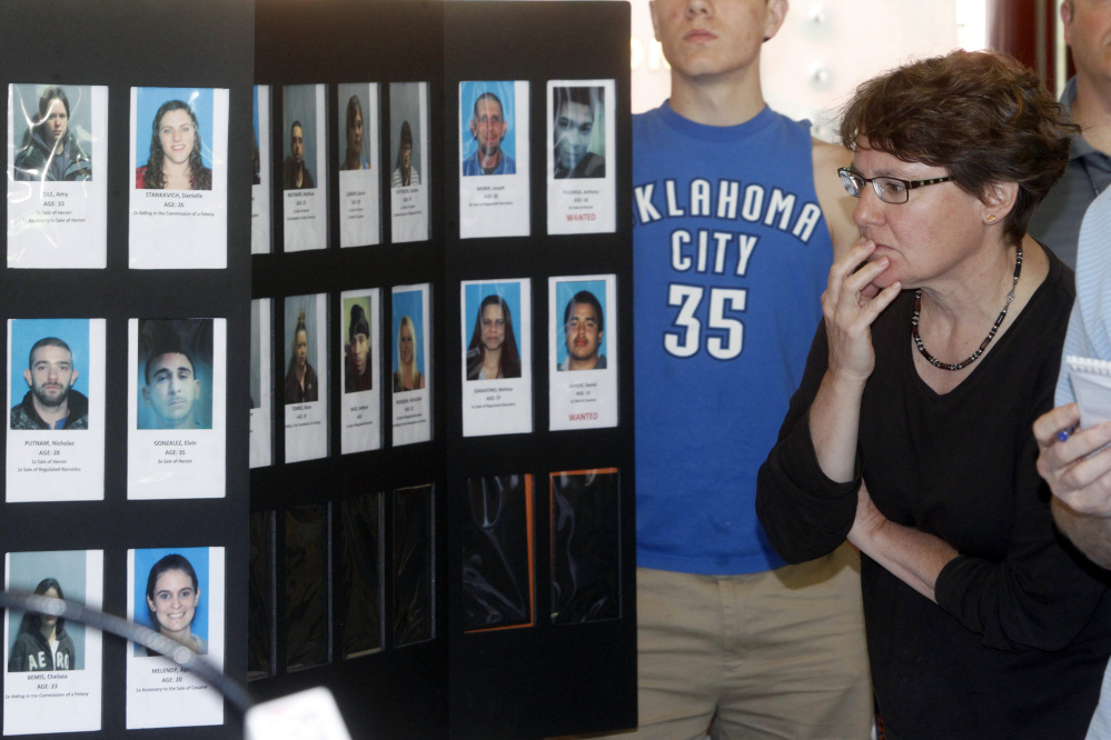 In this June 19, 2013, photo, Springfield, Vt., resident Susan White looks over booking photos displayed at a Vermont State Police news conference to discuss the arrest of 36 people as part of a large drug sweep.