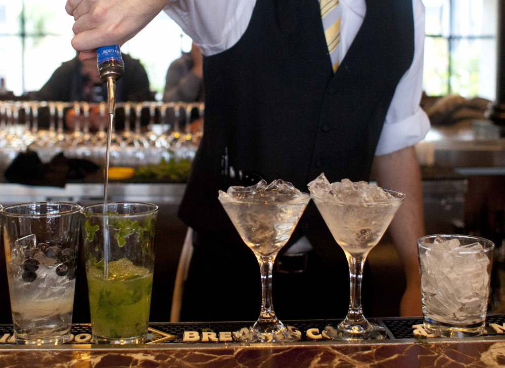 A bartender prepares alcoholic drinks at a restaurant in San Francisco. Middle-age men risk a faster mental decline as they age if they've been drinking heavily for years, new research suggests.