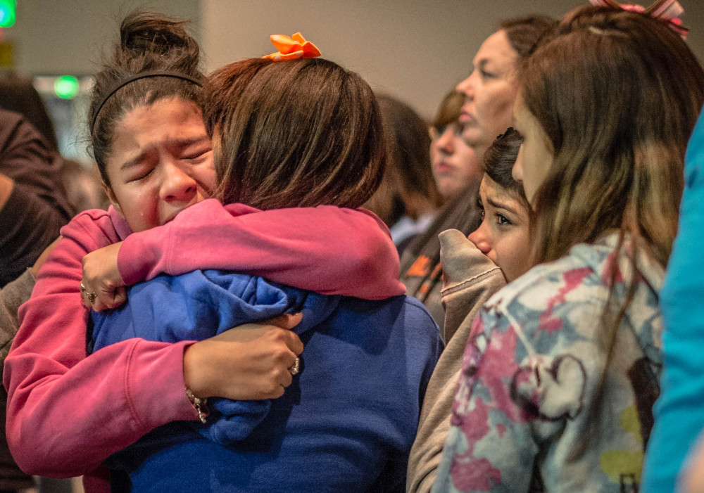 Thirteen-year-old Kimberly Macias cries as she sees schoolmates at a vigil for the victims Tuesday in Roswell, N.M. A 12-year-old New Mexico boy drew a shotgun from a band-instrument case and shot and wounded two classmates at his middle school Tuesday morning before a teacher talked him into dropping the weapon and he was taken into custody, officials and witnesses said.