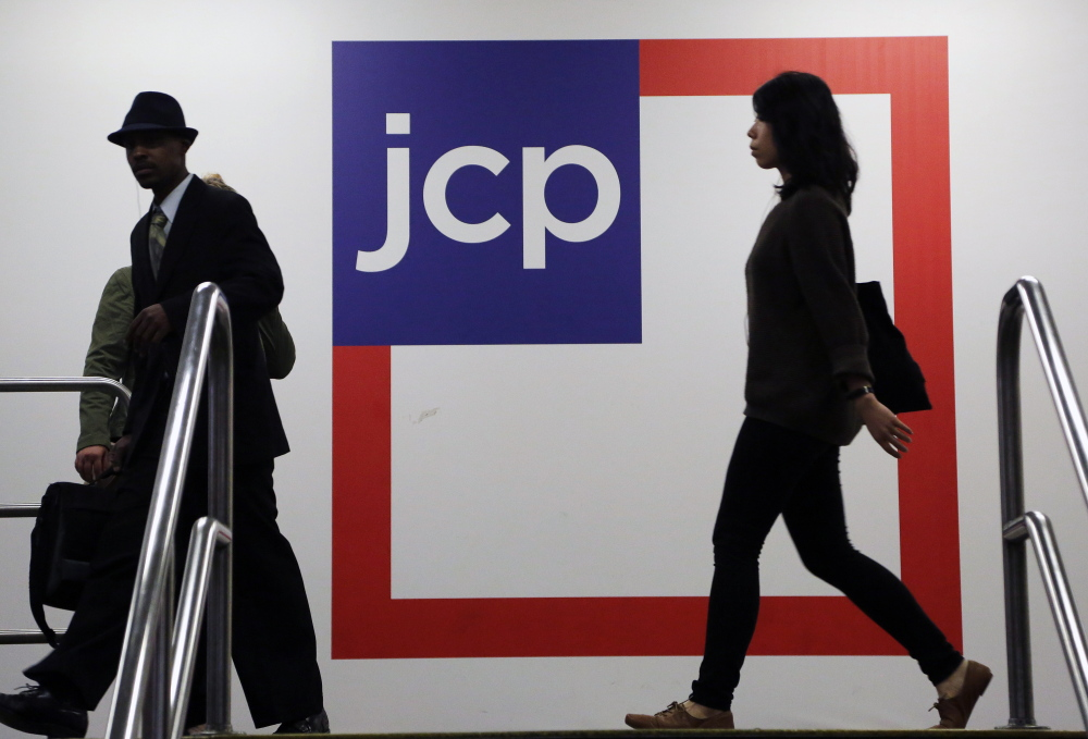 Customers shop at a J.C. Penney store in New York. The company announced cuts Wednesday that should save $65 million annually.