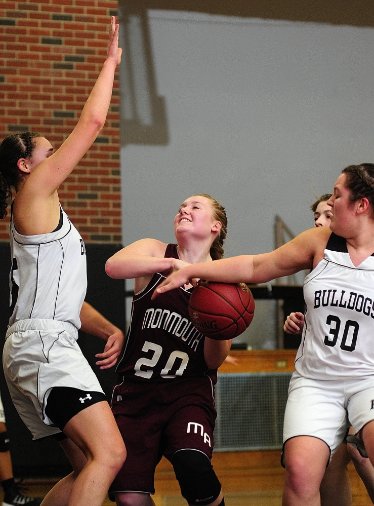 Staff photo by Joe Phelan Monmouth Acadmey junior forward Jenna Davis, middle, is double-teamed by Hall-Dale's Allison Crockett, left, and Molly French during a game on Thursday January 16, 2014 in Hale-Dale High's Penny Memorial Gym in Farmingdale.