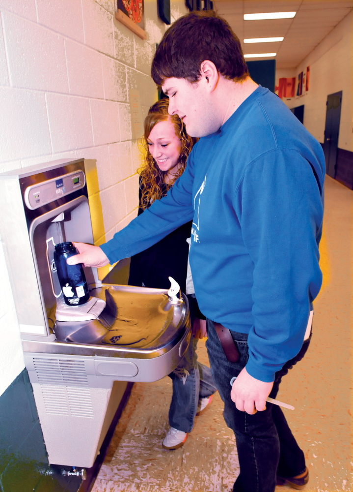 FILL 'ER UP: Carrabec High School students Tyler Pinkham and Skyla Murray fill reusable water bottles Tuesday at a bottle filling station at the Anson school. The students are taking part in an effort to reduce plastic waste.